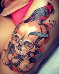 Bird and skull tattoo on leg