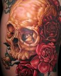 Gold skull with red roses tattoo