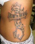 Music cross belly tattoo