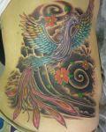 Peacock among flowers tattoo