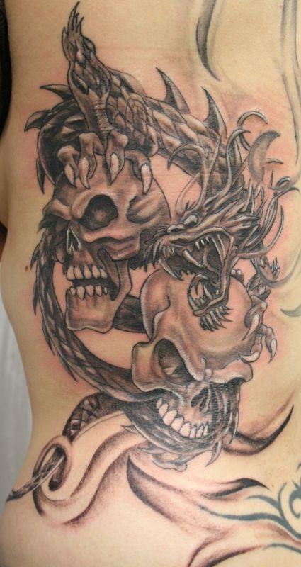 Two skulls and dragon tattoo